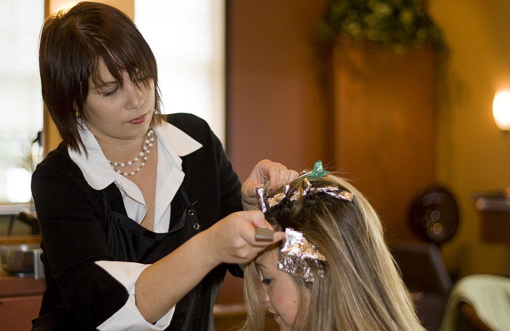 Hairdresser doing highlights with foils