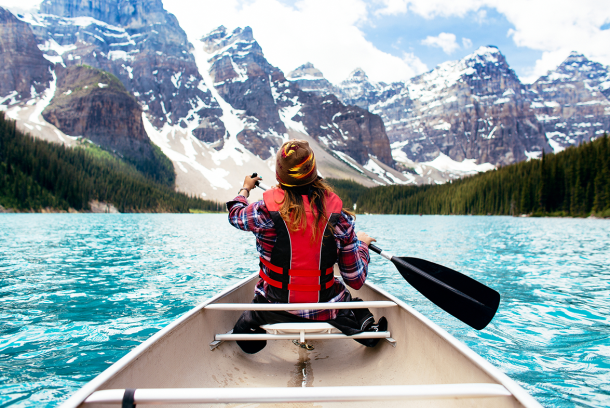 woman canoeing with snowy mountains in the background