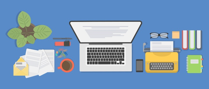 Illustration of a blue desktop with a laptop, plant, typewriter, notebook, books, papers, phone, and eyeglasses on it